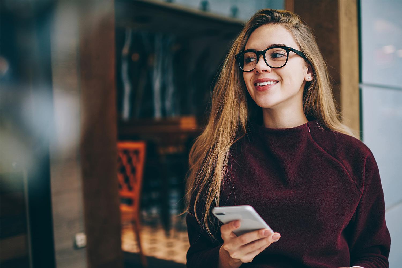 Smilende kvinde med smartphone i hånden