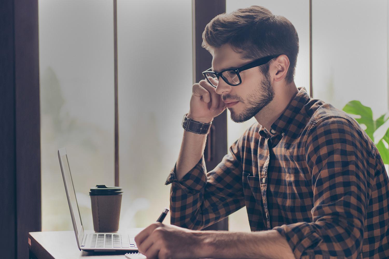 Mand ser koncenteret på laptop