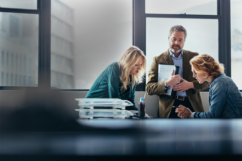 Tre kollegaere kigger på notater