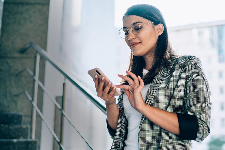 Smilende kvinde taster på smartphone