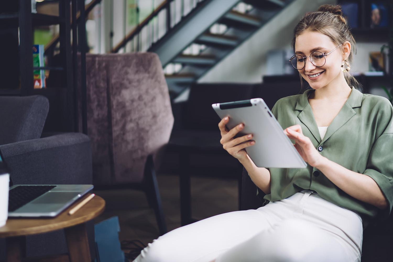 Smilende kvinde bruger iPad